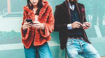 Two Young People Using Their Smartphones To Review Digital Marketing Trends