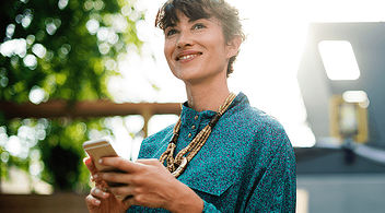 A Smiling Young Woman Writing A Product Review On A BigCommerce Website On Her Phone