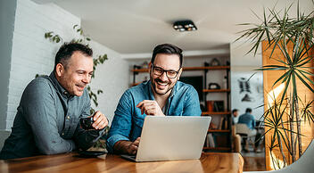 Two Men Smiling And Looking At Computer Screen Featuring Marketing Blog With High Conversions