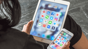 A Person Holding An Ipad And An Iphone With Social Media Apps On Both Screens Used For Digital Marketing And Advertising