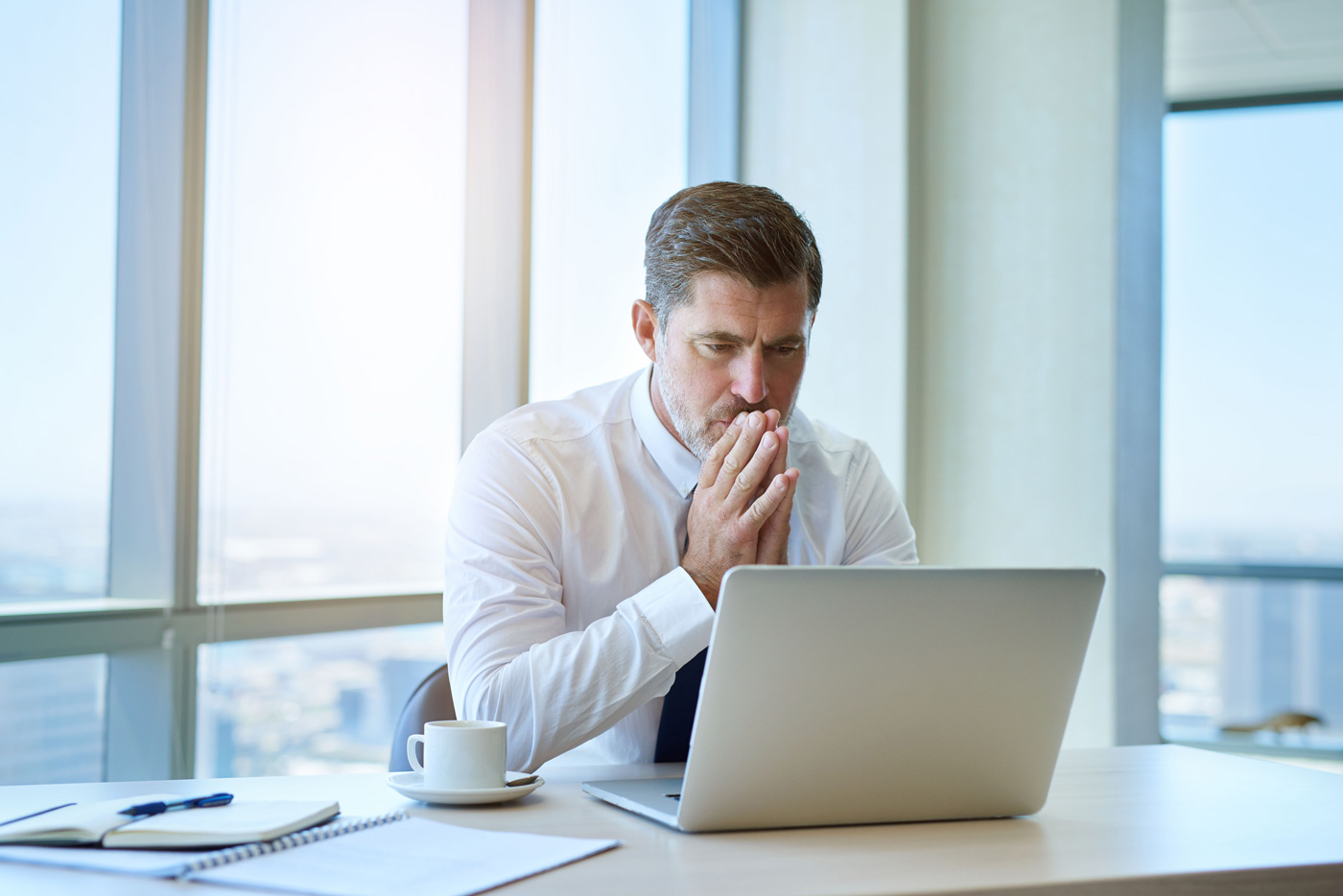 eCommerce Business Owner At His Office Reviewing Data Backup Software On His Laptop