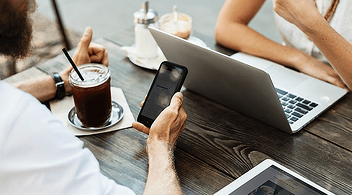 Two People Having Coffee And Working In Their Devices Using Mobile Internet