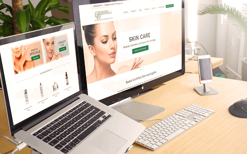 Desk with multiple monitors displaying Grieshaber Dermatology's website