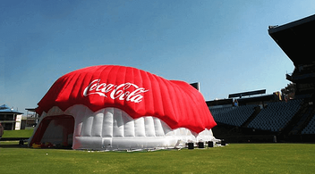 A Coca-Cola Branded Structure Set Up For An Experiential Marketing Event Being Inflated