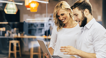 Two Young People Looking At A BigCommerce Website Of A Small Business On A Laptop And Smiling