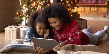 Happy Mother And Daughter In Front Of A Christmas Tree Doing Holiday Shopping On eCommerce Platforms
