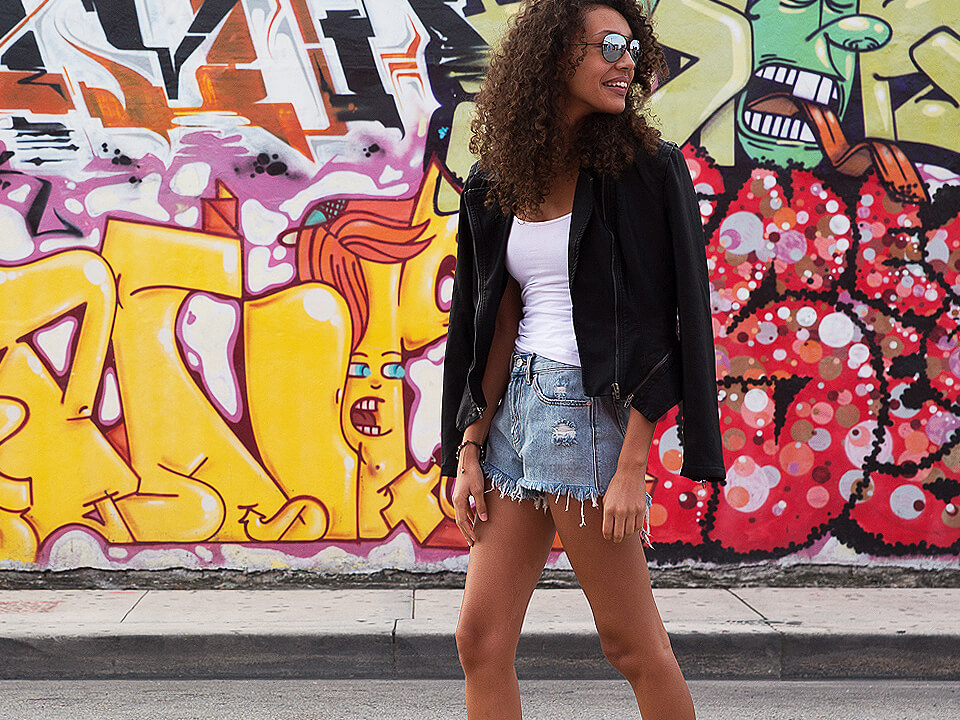 Beautiful Woman With Sunglasses Smiling In Front Of Graffiti Wall