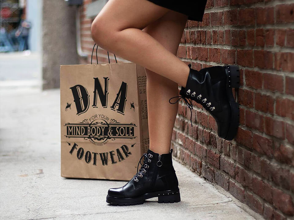Footwear Marketing Agency Photo Of Woman Wearing Boots With Branded Shopping Bag