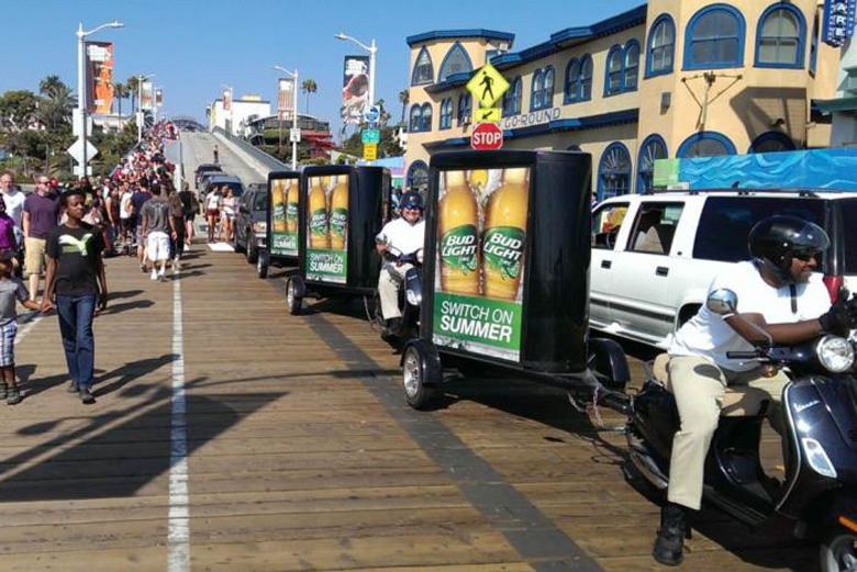 Bud Light Signs Towed By Scooters On A Boardwalk