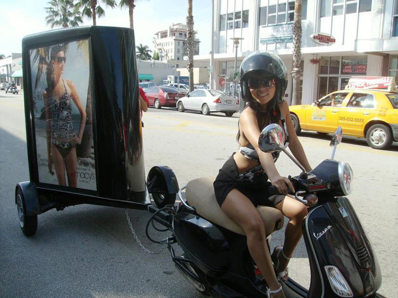 Image of A Girl Driving A Scooter Towing A Custom Sign