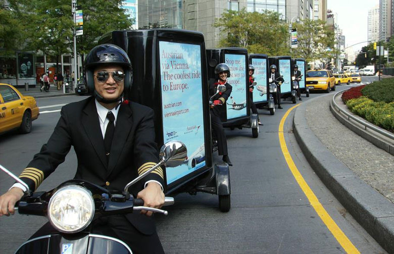 Experiential Marketing Fleet of Five Scooters Towing Signs In Traffic