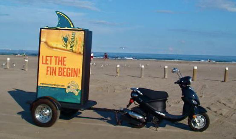 Experiential Marketing Photo of Scooter by the Beach Towing a Trailer With a Beer Advertisement