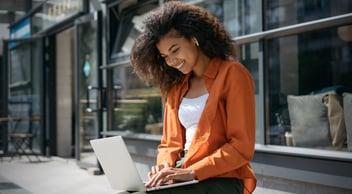 Female Klaviyo Email Marketing Manager Wearing An Orange Cardigan Typing On A Laptop