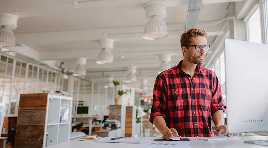Marketing Manager Wearing A Red Shirt Analyzing Mainstream Markets On Computer