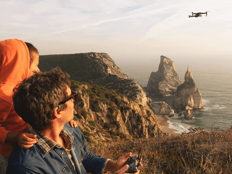 Two Guys Flying A Drone Over Mountains and Cliffs Shown On Website Design Agency Case Study
