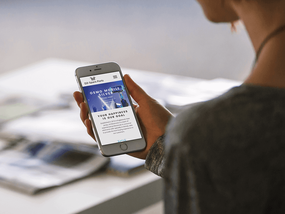 Young Woman Holding SmartPhone Showing Drone Website Design by Web Development Agency