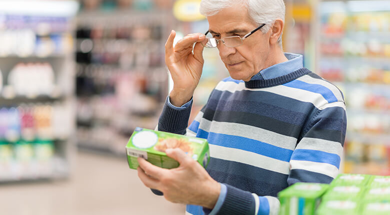 An Older Man Holding Product Package That Is Hard To Read