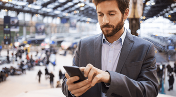 A Man Using His Smartphone To Review ROI For The Company At An Experiential Marketing Event