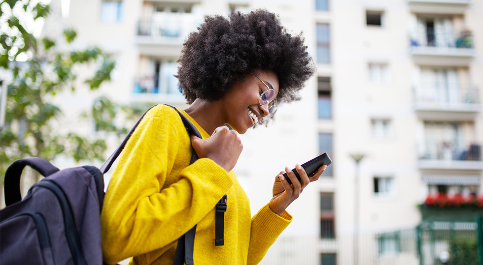 Teenager Wearing Yellow Top And Checking Social Media On Her Smartphone