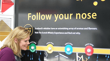 Woman Smelling An Aromatic Sample At A Multisensory Experiential Marketing Event
