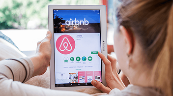 A Woman On A Tablet Installing Popular Airbnb App Promoted By The Company's Marketing Tactics For Growth