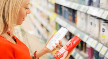A Woman Choosing Between Two Trending Packaging Designs At A Supermarket