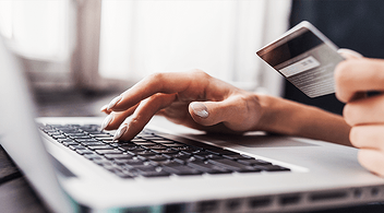 A Woman Making An eCommerce Website Purchase With Credit Card Using A Laptop