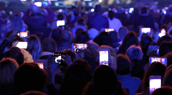 A Crowd At An Event Holding Up Their Phones With Event Mobile Apps on Screens