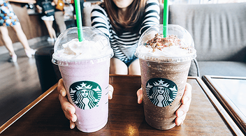 A Loyal Female Customer Holding Two Starbucks Beverages During Marketing Promotion On Location