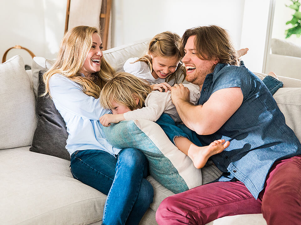 Image Of Happy Family Laughing On A White Sofa As Part Of A Textile Marketing Promotion