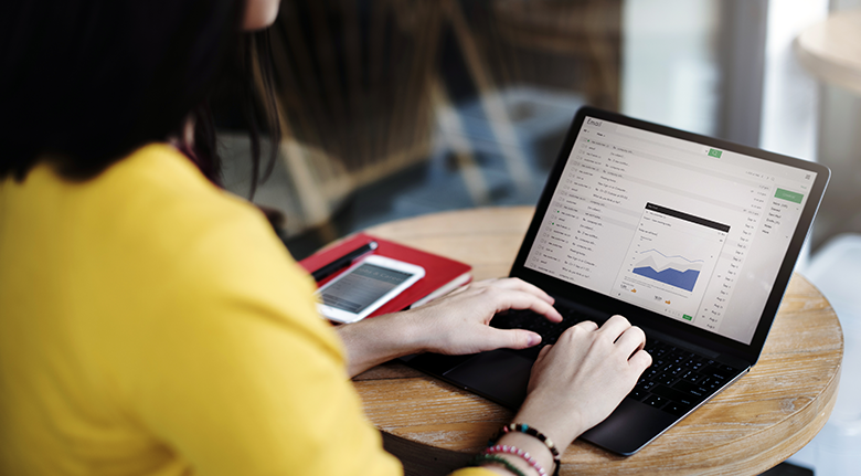 Woman In Yellow Top Typing On A Laptop Screen While Making A Custom BigCommerce Template