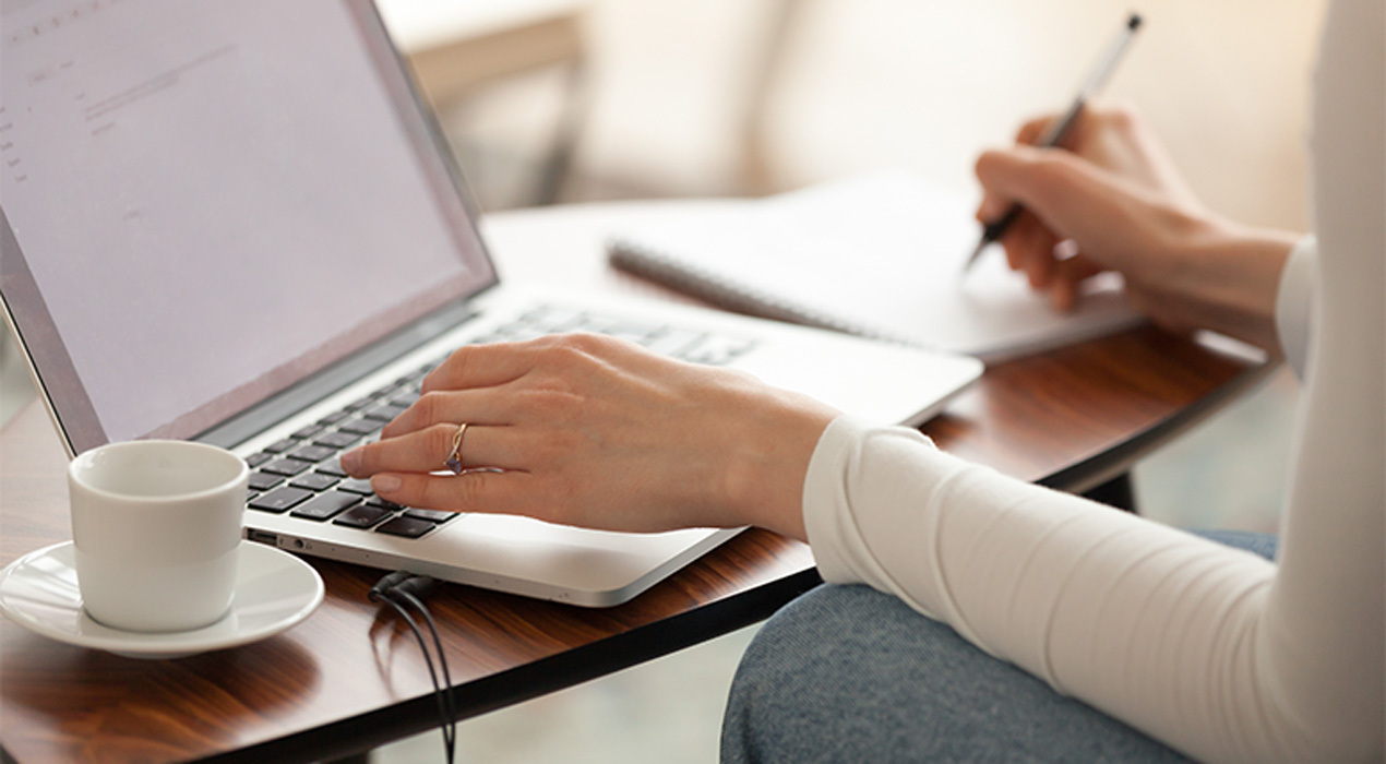 Woman Writing A Blog On Laptop And Taking Notes