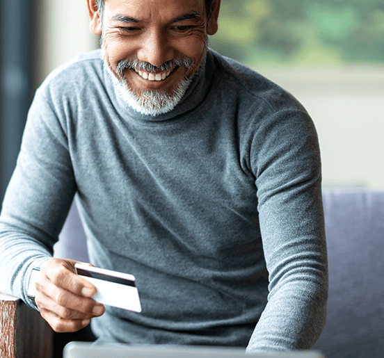 Ecommerce Web Design Agency Image of Smiling Man Holding a Credit Card
