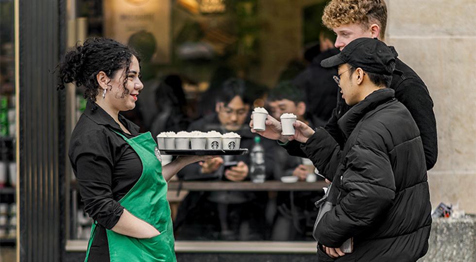 Starbucks Worker Offering Samples to Customers