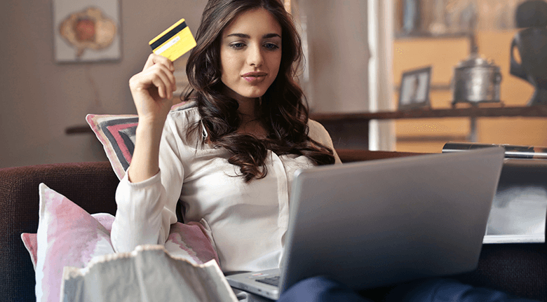 Young Woman Holding Credit Card While Looking At Laptop