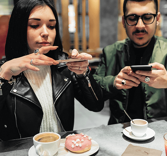 Man And Woman Taking Pictures Of Food As Part Of An Influencer Marketing Agency