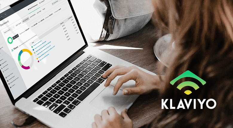 Klaviyo Logo With A Woman Using A Laptop With Klaviyo App On Screen