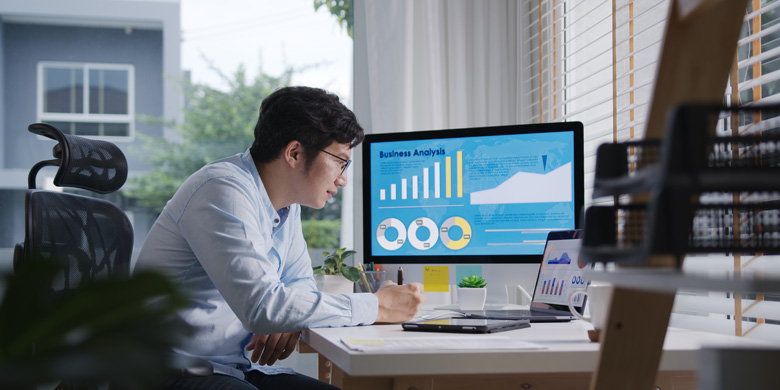 Man Sitting At The Table In Front Of Two Monitors Tracking Conversions On Shopify