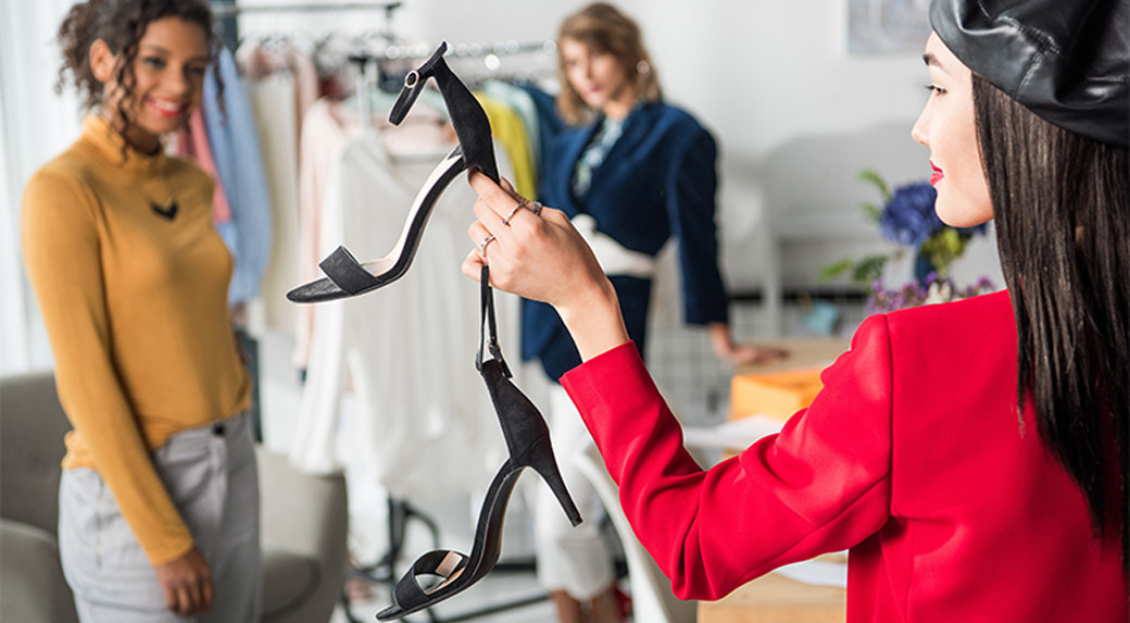 Sales Assistant in red Jacked Showing Shoes to Clients
