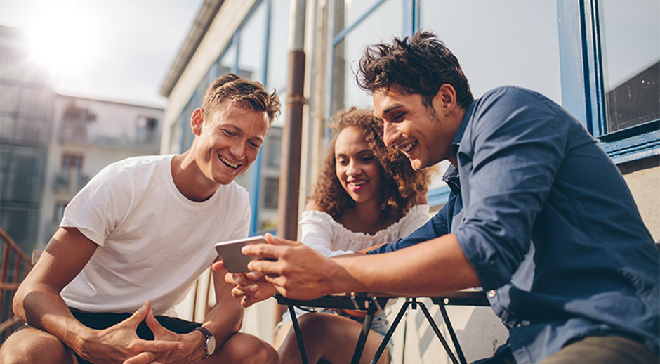 Friends Looking At Fun Social Media Posts On Mobile