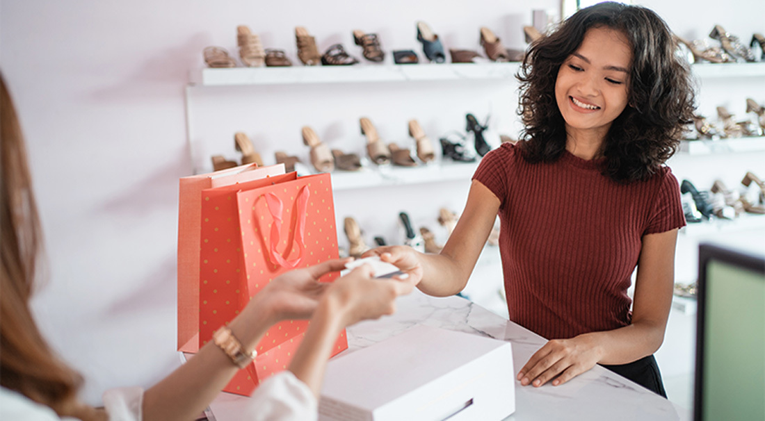 Shoe Store Manager Giving Packaged Products To A Client